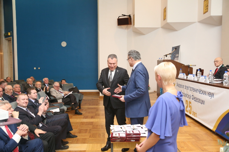 AES RF President Pavel Butyrin is handing the Medal of Merit for Electrical Engineering to Alexander Slavinsky